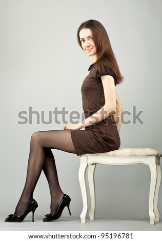 Elegant young smiling brunette sitting on a banquette; neutral background - stock photo