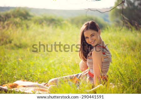Elegant young smiling woman posing in sunny park - stock photo