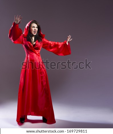 Elegant young witch in a red clothes cast magic spell  - stock photo