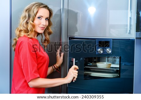 Elegant young woman cooking in the kitchen at home. Healthy eating. Home interior. Furniture. - stock photo