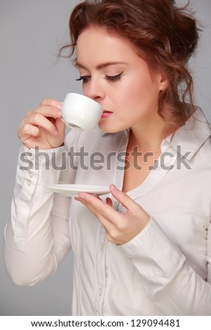 Elegant young woman drinking coffee in the morning on grey background