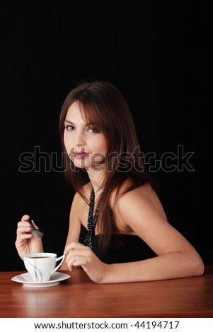 Elegant young woman drinking coffee, isolated on black