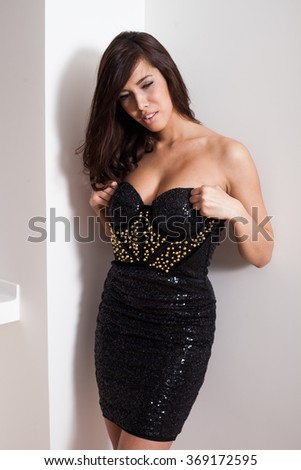 elegant young woman in black cocktail dress prepare to go out, indoor shot