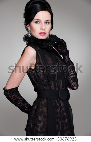 elegant young woman in black dress posing against grey background - stock photo