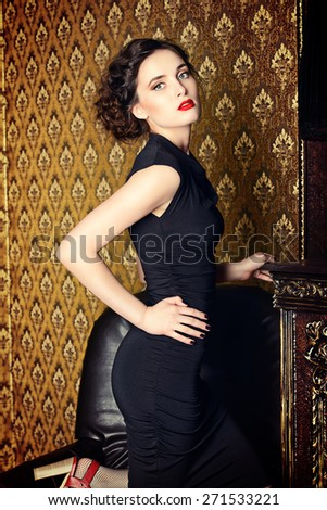 Elegant young woman in black evening dress posing in vintage interior. Fashion shot. - stock photo