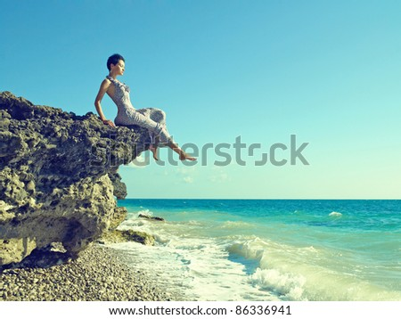Elegant young woman in dress sits on rocky shore - stock photo