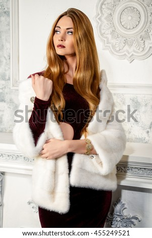 Elegant young woman in evening dress and mink fur jacket posing in vintage interior. Jewellery. Fashion shot. - stock photo