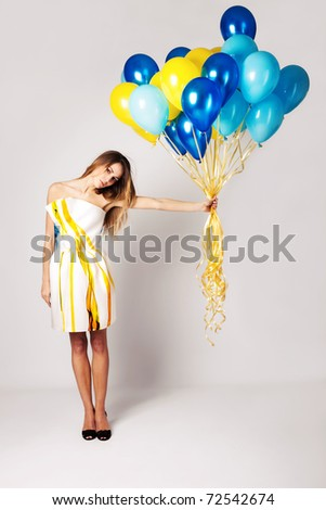 elegant young woman in silky dress holding balloons, studio shot, full body shot