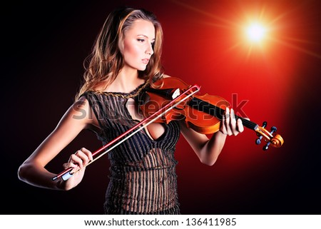 Elegant  young woman playing her violin with expression. - stock photo