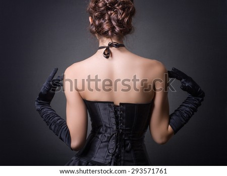 Elegant young woman posing in a black corset back. - stock photo