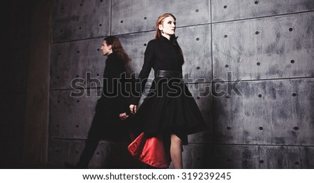 Elegant young woman posing in coat, fast-moving man on the background, blurred silhouette - stock photo