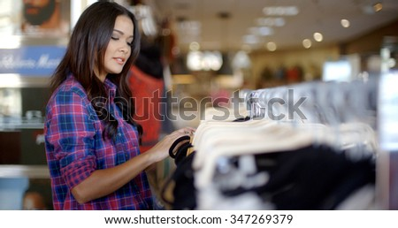 Elegant young woman shopping in clothes store at fashion mall