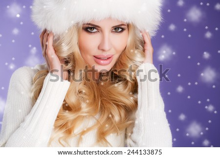 Elegant young woman with make-up and hairstyle posing in knitted sweater and fur winter white hat on violet background. Studio shot. Snowing around. Snow. Winter. - stock photo