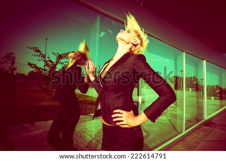 elegant young  woman with short blonde hair in black blazer throw back hair shot in the city by the glass wall - stock photo
