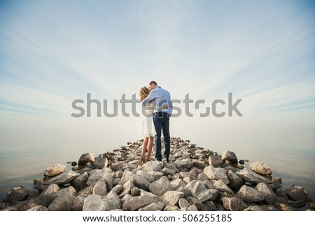 Elegant young women in white dress tenderly embraces loving man on the rocky road, on the background of the light blue sky