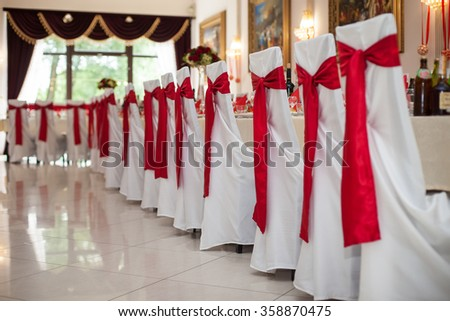 Elegantly catered wedding reception hall with red ribbons on luxury white chairs and marble floor - stock photo