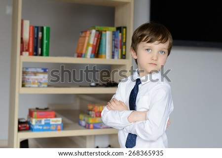 Elegantly dressed in a white shirt and tie little boy. Standing in front of a shelf of books - stock photo