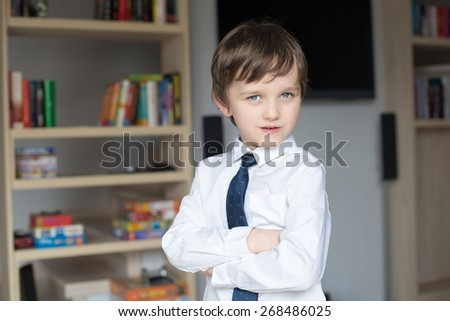 Elegantly dressed in a white shirt and tie little boy stands in front of a shelf of books - stock photo