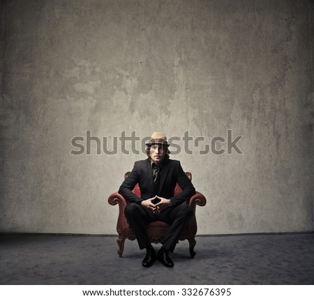 Elegantly dressed man sitting in an armchair