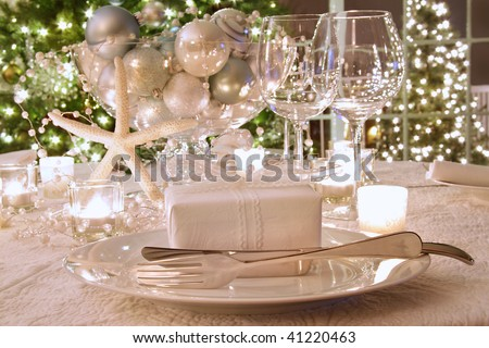 Elegantly lit  holiday dinner table with wine glasses and white ribbon gift - stock photo