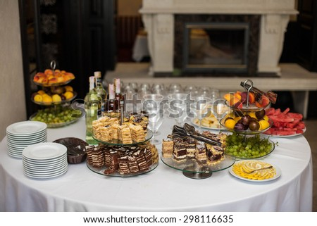 elegantly tastefully decorated buffet of delicious sweets, drinks and fruits - stock photo