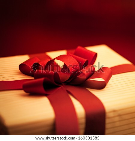 Elegantly wrapped present with a red ribbon. - stock photo