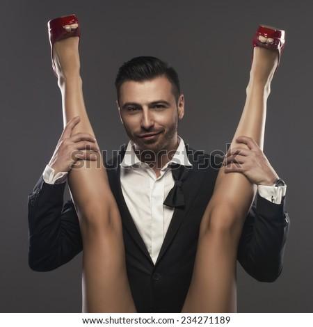 Elegenat man sitting and is spreading a woman's legs - stock photo