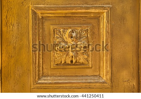 Element of old painted wood doors texture, grunge background, cracked paint. Gold paint on wood. Vintage retro street door with ornaments. Elaborately carved pattern on the wooden door. - stock photo