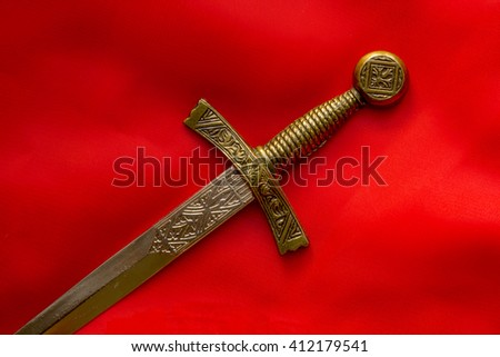 element of the ancient dagger handle on a red background - stock photo