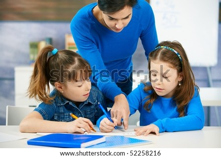 Elementary age children listening to female teacher in school classroom. - stock photo