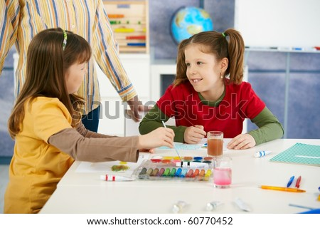 Elementary age children sitting around desk enjoying painting with colors in art class at primary school classroom.? - stock photo