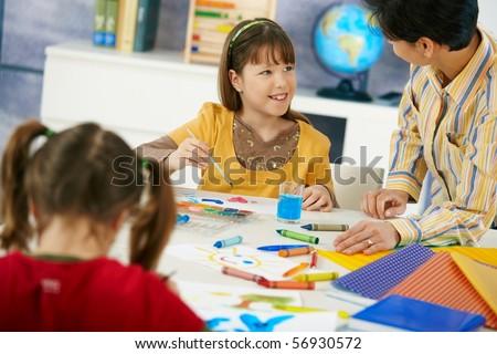 Elementary age children sitting around desk enjoying painting with colors in art class in primary school classroom.? - stock photo