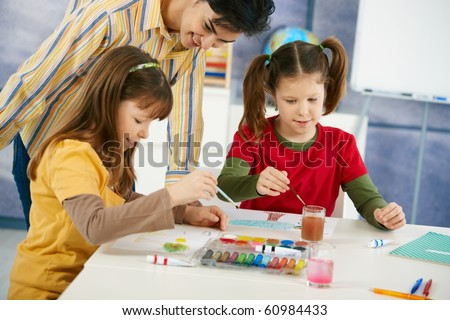 Elementary age pupils sitting around desk enjoying painting with colors in art class at primary school classroom.? - stock photo