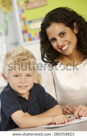 Elementary Age Schoolboy Reading Book In Class With Teacher - stock photo
