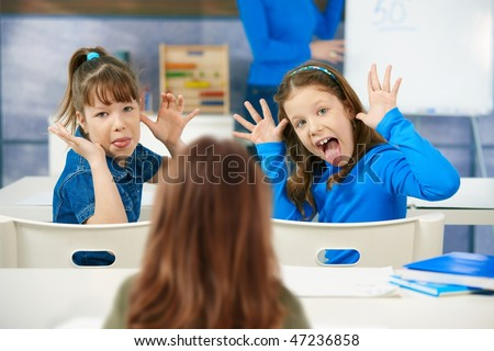 Elementary age schoolgirls pulling faces to girl sitting behind, teacher at blackboard in background. - stock photo