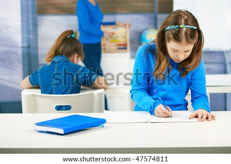 Elementary age schoolgirls writing tests at class seated aside, teacher standing in the background. - stock photo