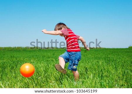 Elementary aged boy kicking ball in the field - stock photo