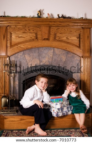 Elementary brother and sister leaning on a stack of wrapped Christmas gifts on their home's hearth.