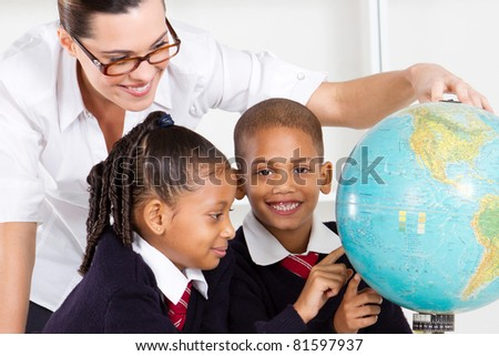 elementary geography teacher and students looking at globe in classroom