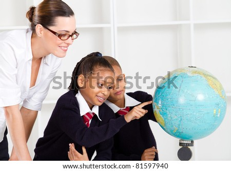 elementary geography teacher and students looking at globe in classroom - stock photo