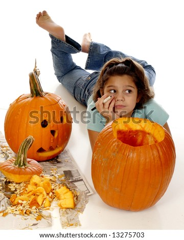 Elementary girl thinking about what sort of face she'll create on her Halloween pumpkin.