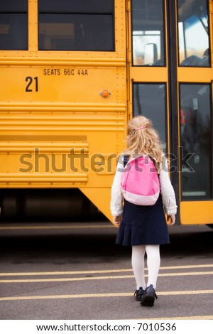 Elementary girl with a back pack heading toward the school bus.