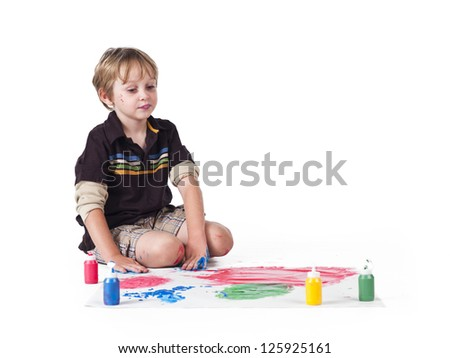 Elementary kid doing painting against white background. - stock photo