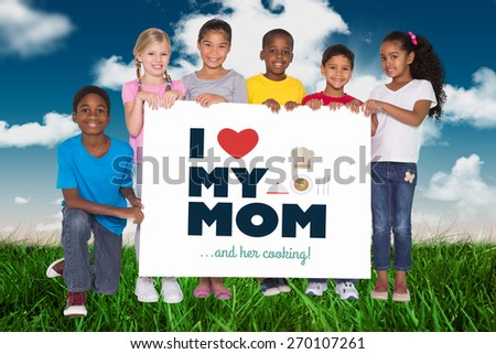 Elementary pupils showing card against field and sky - stock photo