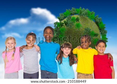 Elementary pupils smiling against bright blue sky with clouds with globe - stock photo