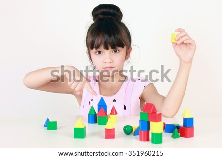 Elementary school aged girl plays with colored blocks. - stock photo
