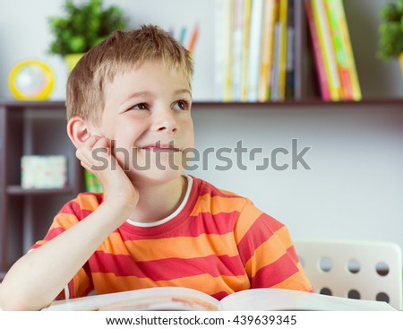 Elementary school boy at classroom desk reading book