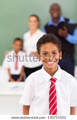 elementary school boy in front of teachers and classmate in classroom