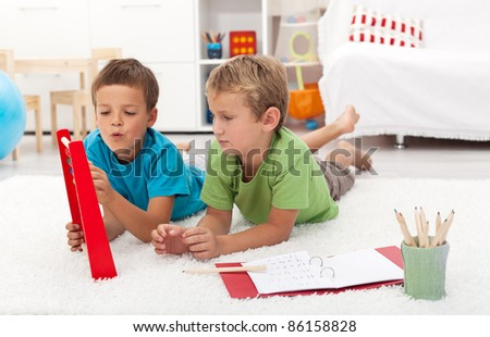Elementary school boys doing math exercises at home - laying on the floor - stock photo
