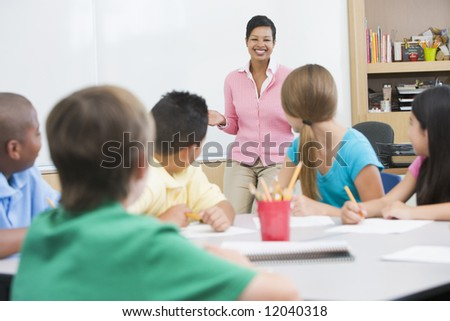 Elementary school classroom with teacher standing at board